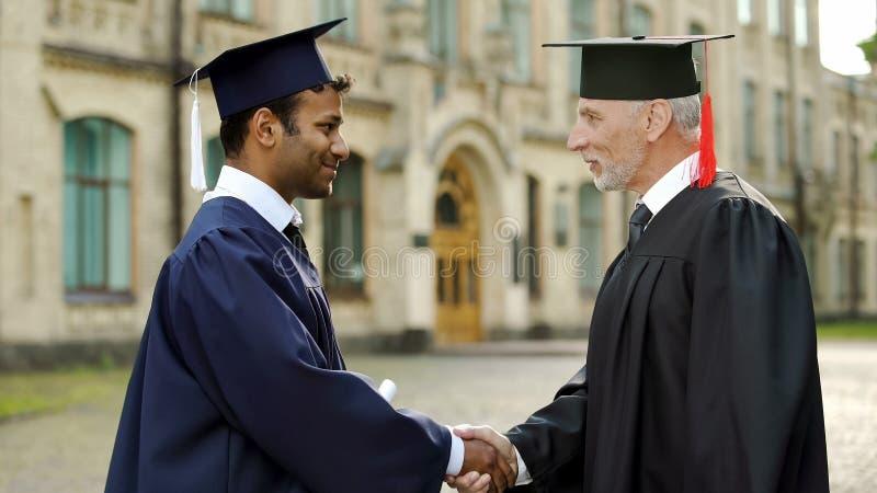 Ansedd professor som ger diplomet till den manliga studenten som skakar handen, lyckad framtid arkivbilder