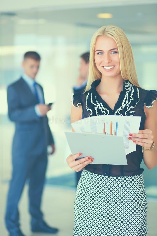 Anseende för affärskvinna i förgrund med en mapp i henne händer royaltyfri bild