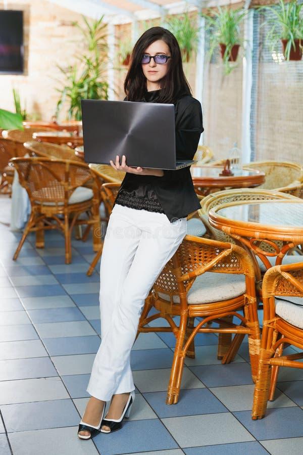 Anseende för affärskvinna i restaurang med bärbara datorn i händer royaltyfri bild