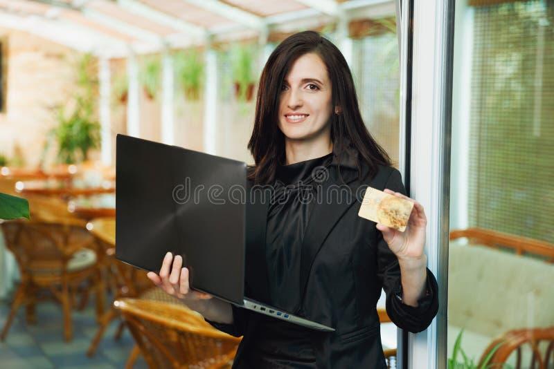 Anseende för affärskvinna i restaurang med bärbara datorn och visningCR royaltyfria bilder