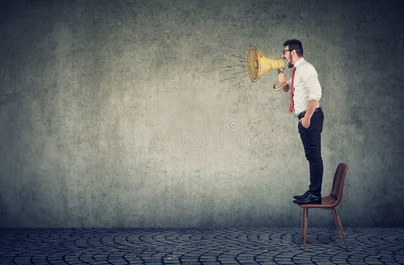 Anseende för affärsman på en stol och skrika in i en megafon royaltyfria bilder