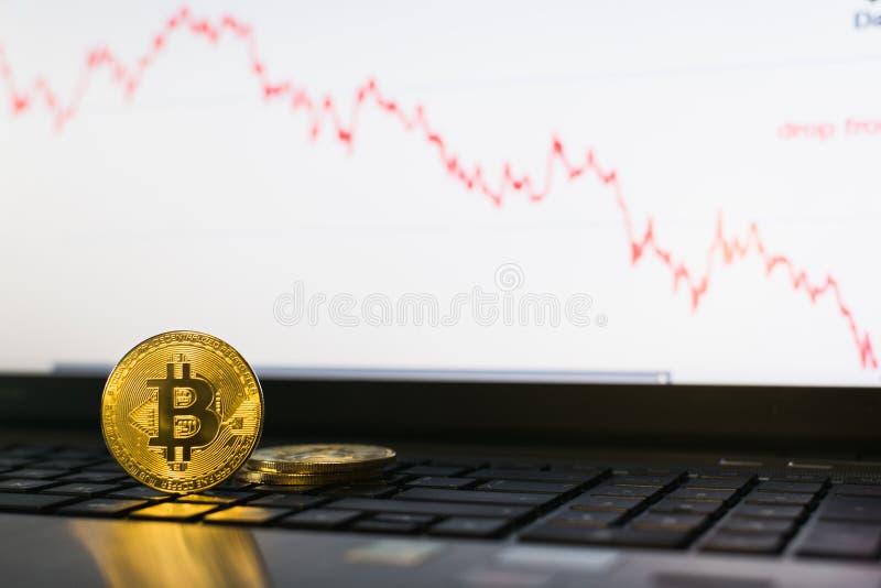 Anseende för Bitcoin cryptocurrencymynt på bärbar datortangentbordet med det nedgående diagrammet på bakgrund arkivbilder