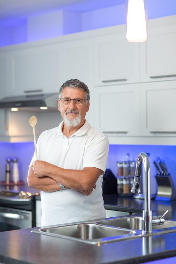 Anseende för hög man i hans moderna kök royaltyfria bilder