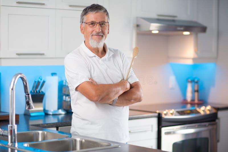 Anseende för hög man i hans moderna kök royaltyfri foto