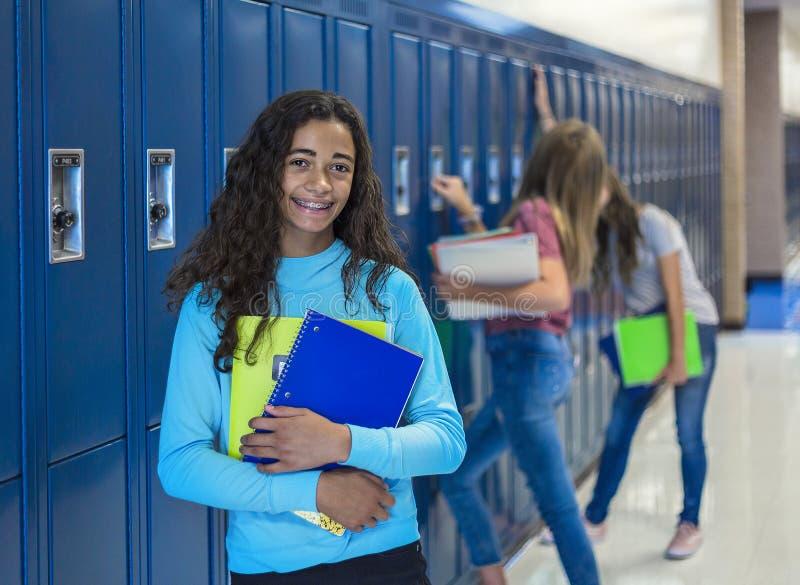 Anseende för Junior High skolastudent vid hennes skåp i ett skolahall arkivfoton