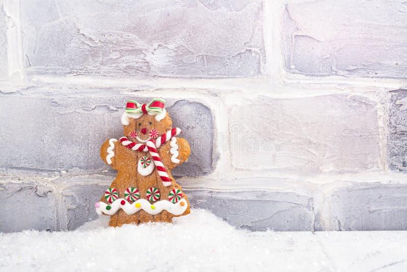 Anseende för kaka för pepparkakaman i en hög av snö nära den vita tegelstenväggen vita röda stjärnor för abstrakt för bakgrundsju arkivfoto