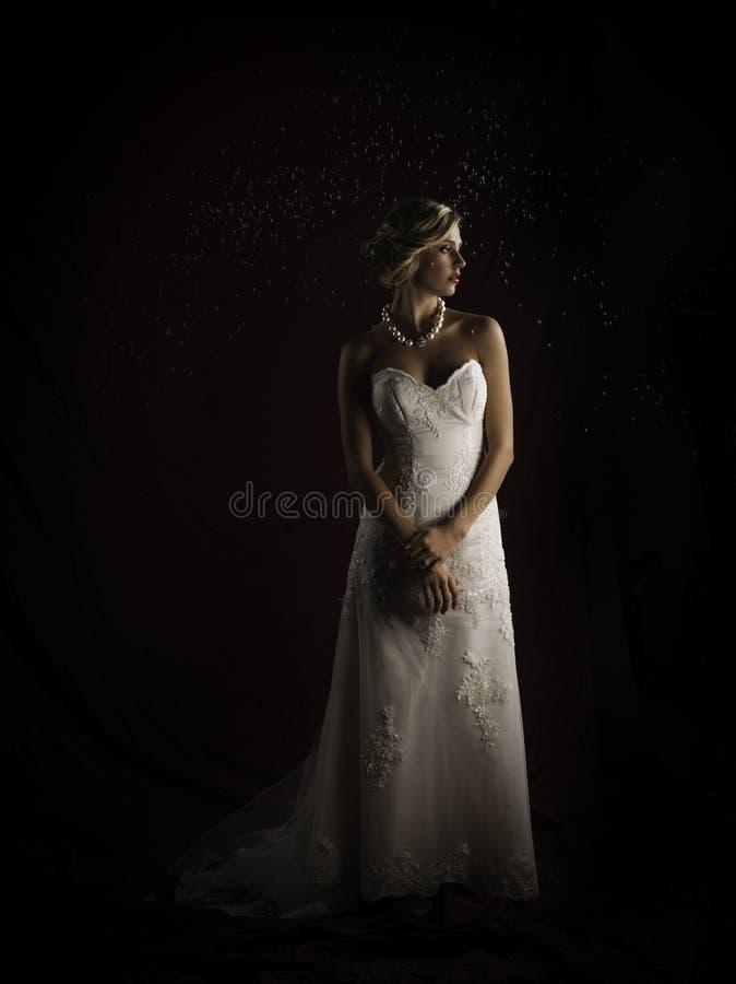 Anseende för kappa för bröllop för tappning för härlig blond brud bärande axelbandslöst i regnet arkivfoton