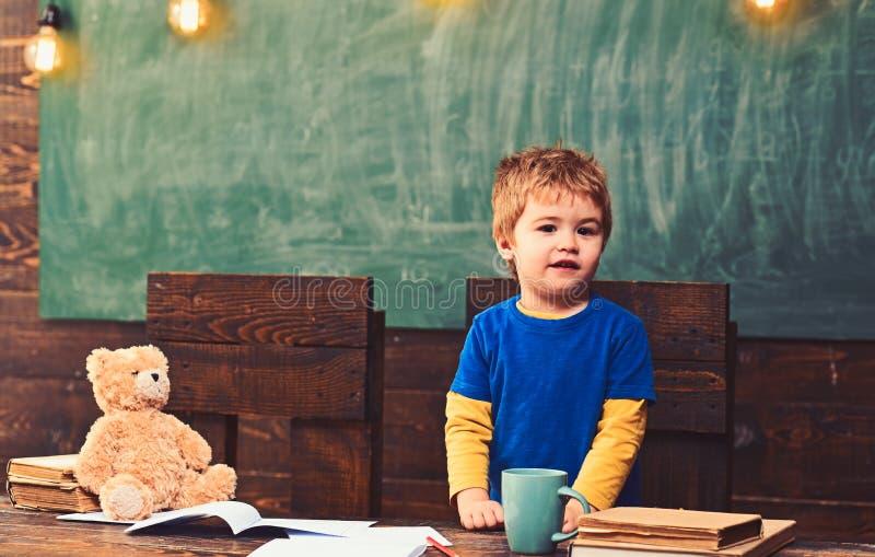 Anseende för liten unge bak träskrivbordet Mörk wood tabell med förskriftsböcker, nallebjörnen, koppen och högen av böcker indivi royaltyfri bild
