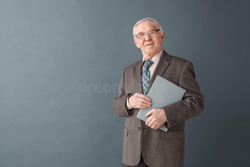 Anseende för studio för exponeringsglas för lärare för hög man som bärande isoleras på den gråa hållande boken som ser den funder royaltyfria bilder