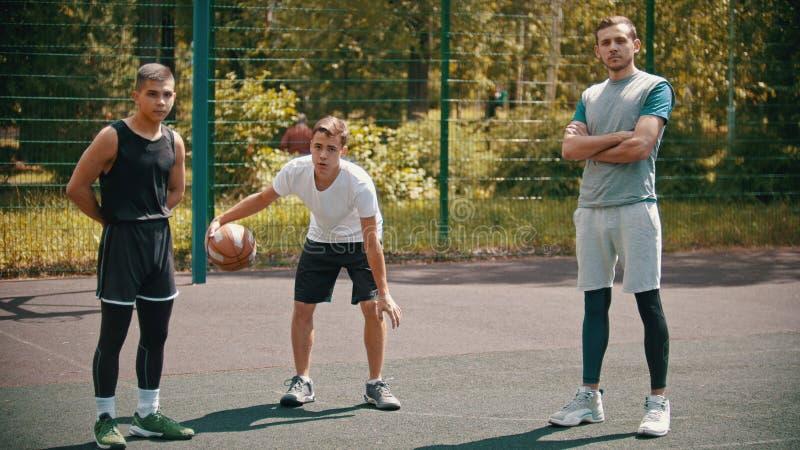 Anseende för tre sportsmens på basketdomstolen utomhus och se i kameran - ett av dem som spelar med en boll royaltyfri fotografi