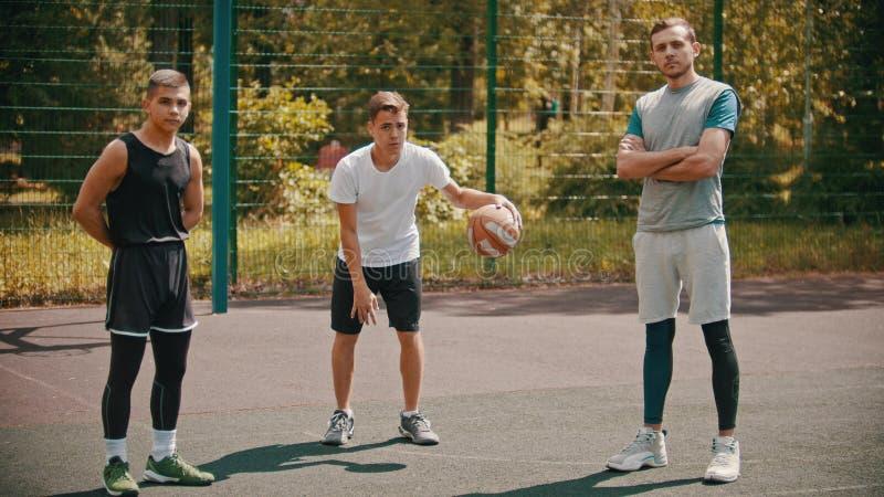 Anseende för tre sportsmens på basketdomstolen utomhus och se i kameran royaltyfri foto