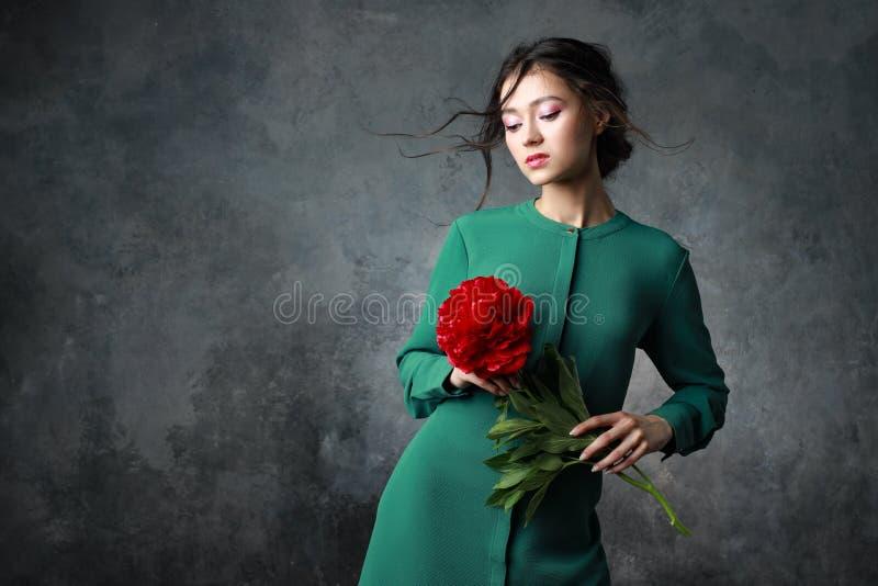Anseende för ung dam med en pionblomma i händer arkivfoto