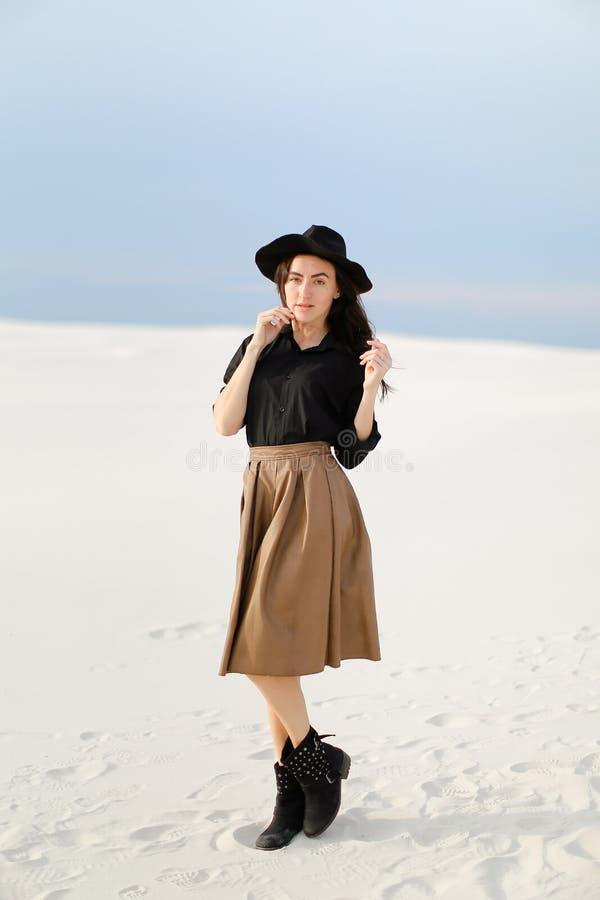 Anseende för ung dam på snö, den bärande kjolen, den svarta blusen och hatten, monophonic bakgrund royaltyfri bild