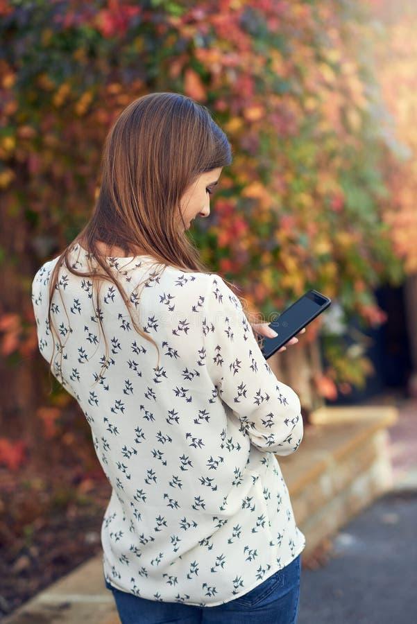 Anseende för ung kvinna i en höstgata som smsar på hennes mobiltelefon arkivbilder
