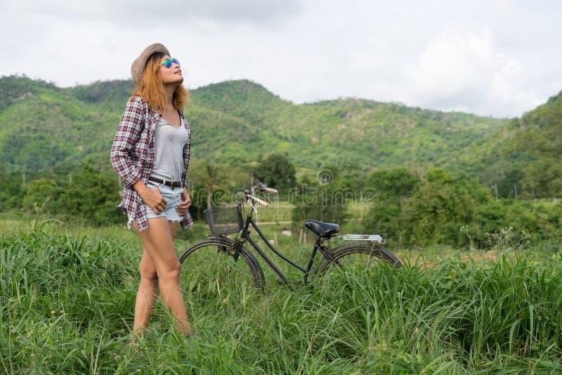 Anseende för ung kvinna med hennes cykel royaltyfria bilder
