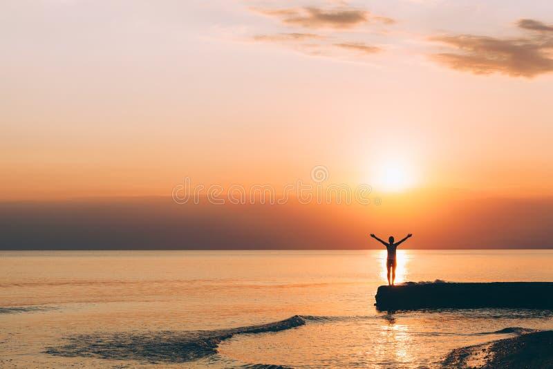 Anseende för ung kvinna med lyftta armar i solnedgång arkivfoto