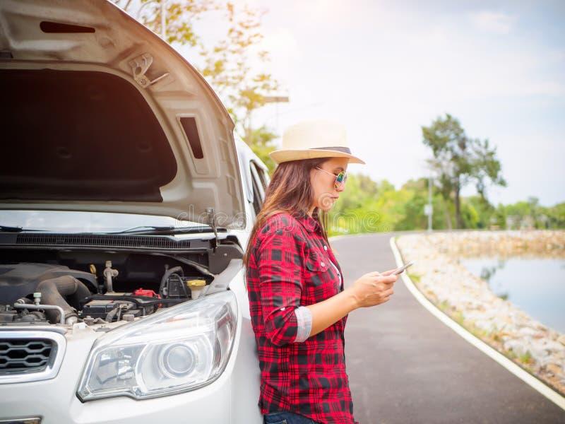 Anseende för ung kvinna på sidan av vägen med den brutna bilen royaltyfri foto