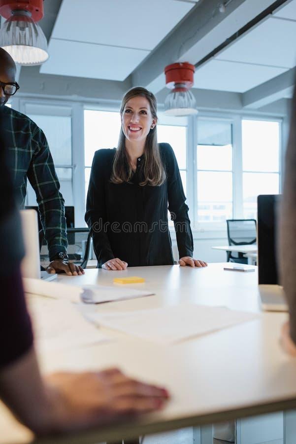 Anseende för ung kvinna på tabellen med kollegor under ett möte fotografering för bildbyråer