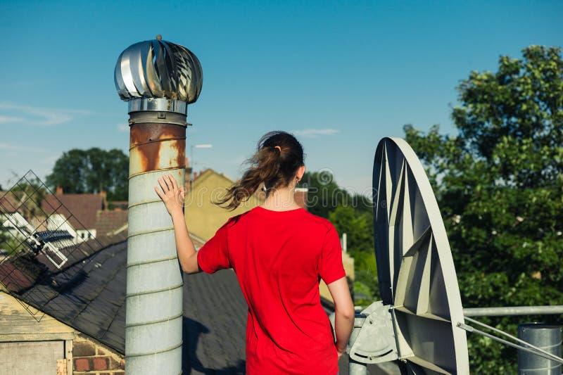 Anseende för ung kvinna på taket vid lampglaset fotografering för bildbyråer