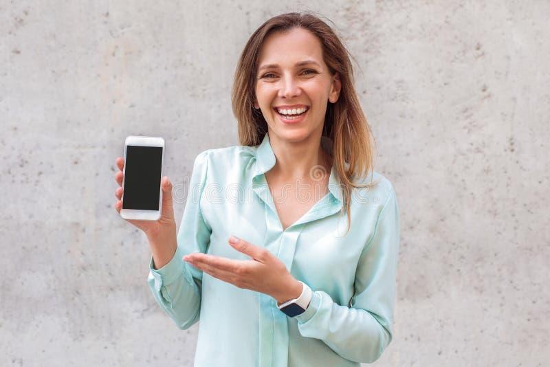 Anseende för ung kvinna på väggen som pekar på skärmen av smartphonen som skrattar som är gladlynt royaltyfri bild