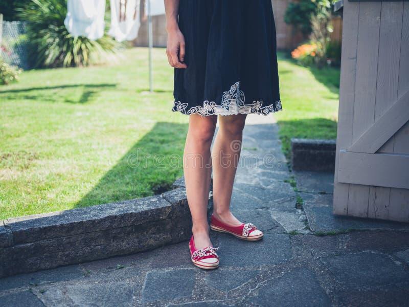 Anseende för ung kvinna vid ett skjul i trädgård arkivfoto
