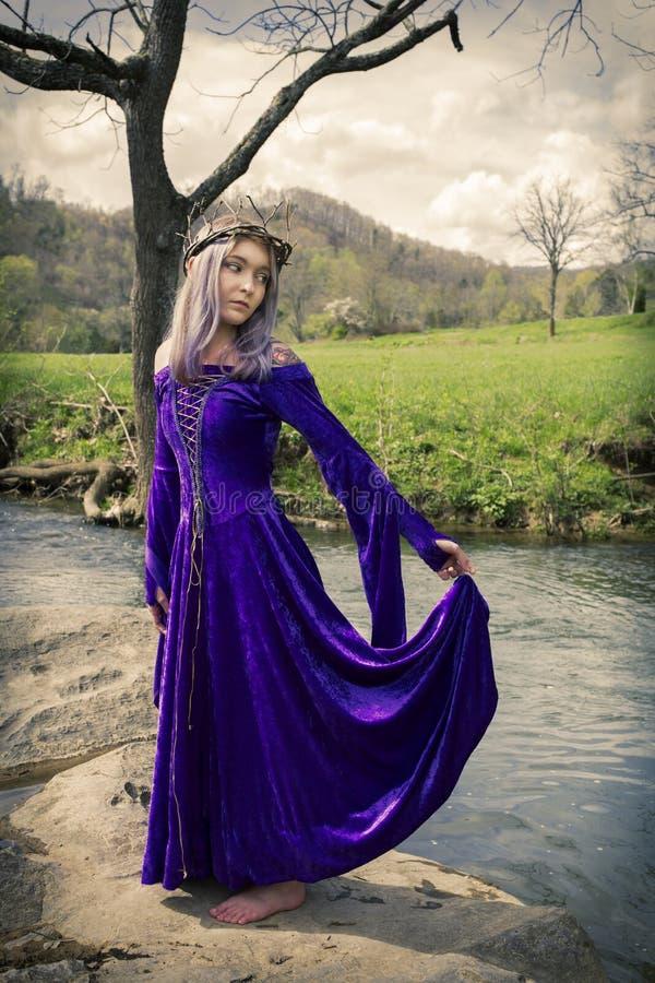 Anseende för ung kvinna vid floden i en purpurfärgad kappa royaltyfri fotografi