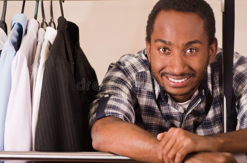 Anseende för ung man för Headshot stiligt inom garderob med kläder som lutar över metallpolen som ler till kameran, mode royaltyfri foto