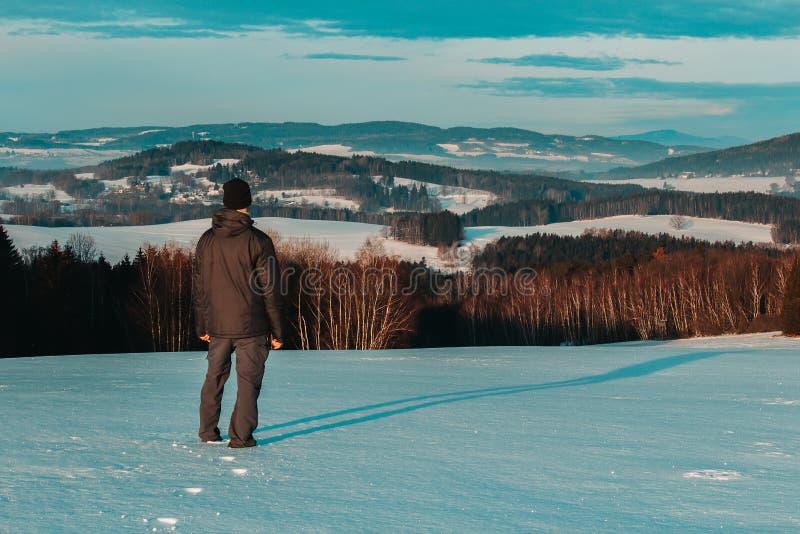 Anseende för ung man i det tjeckiska landskapet för vinter som ser till dalen arkivfoto