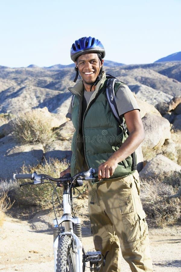 Anseende för ung man med mountainbiket mot kullar royaltyfria bilder