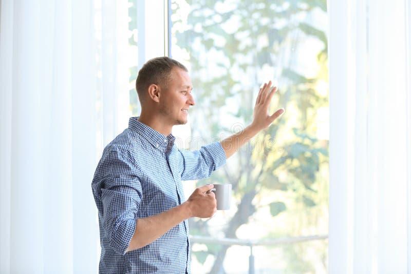 Anseende för ung man nära fönster med öppna gardiner royaltyfria foton