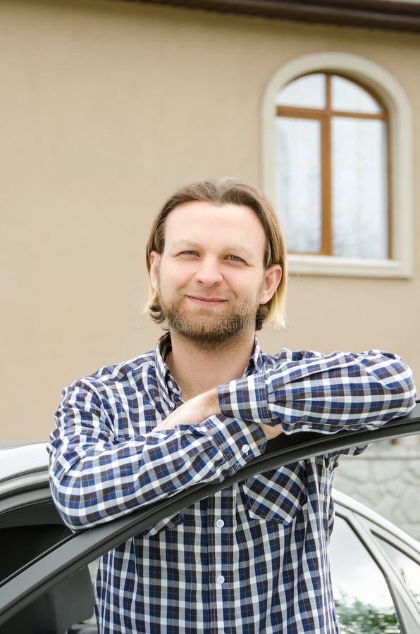 Anseende för ung man nära hans bil och hus och le arkivfoto