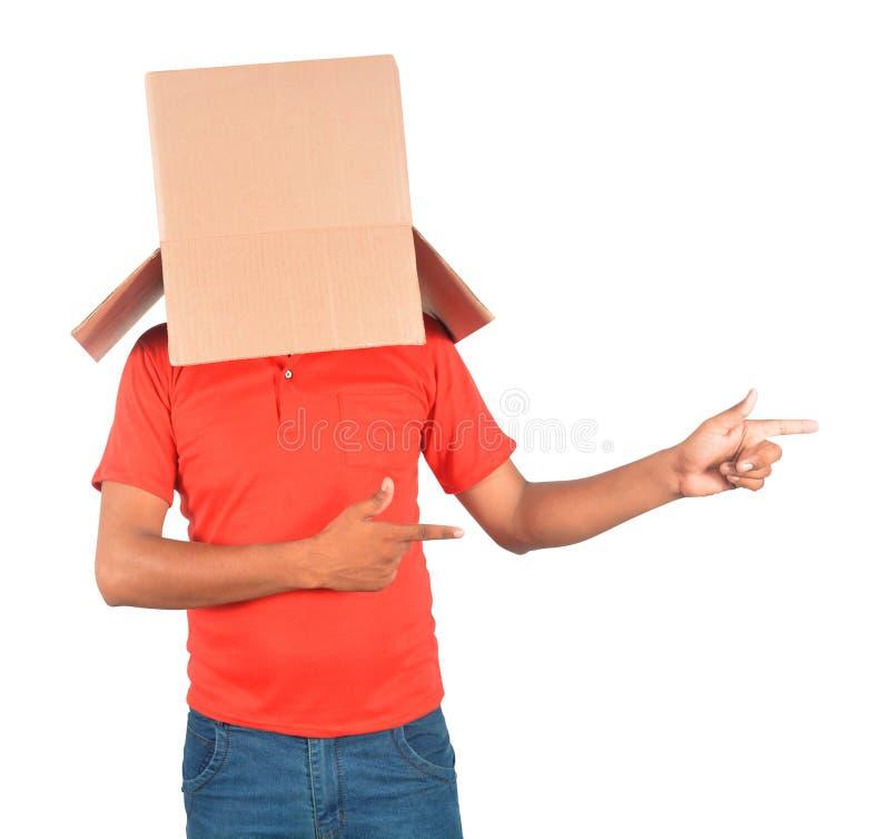 Anseende för ung man och göra en gest med en kartong på hans hea arkivfoto
