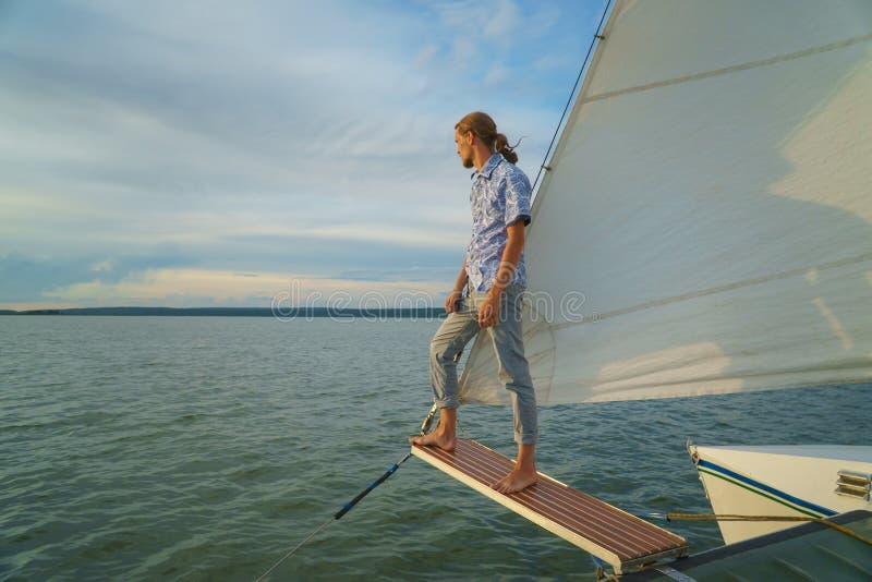 Anseende för ung man på framdel av yachten och att se havet arkivfoto