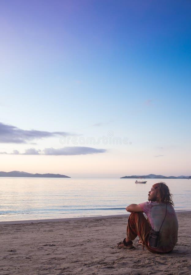 Anseende för ung man på kustlinjen och tycka om arkivbilder
