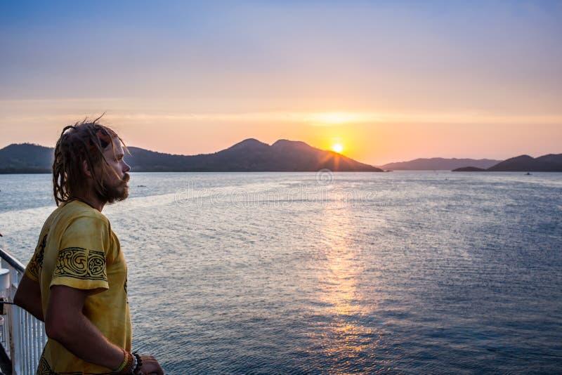 Anseende för ung man på kustlinjen och tycka om arkivfoto