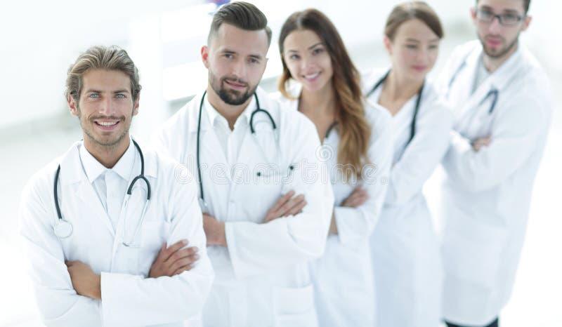 Anseendet för medicinskt lag med armar korsade på en vit bakgrund arkivbild