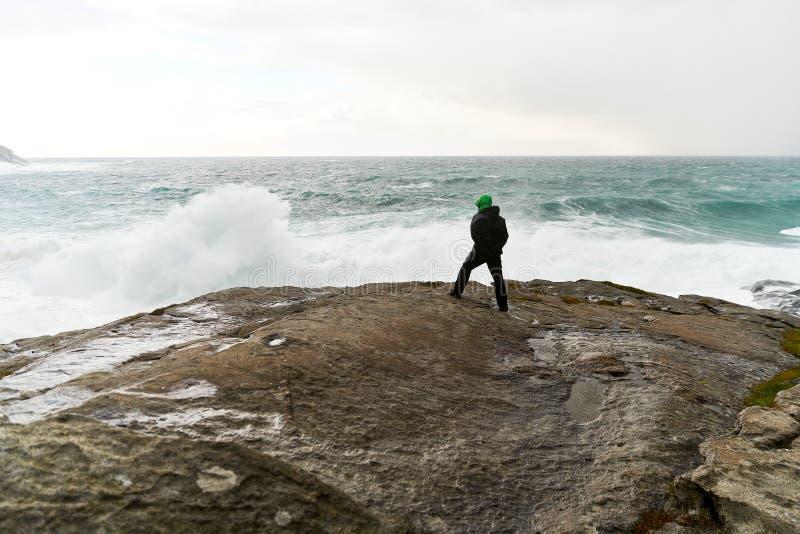 Anseendet för ung man på klippor framme av det lösa havet med vågor som kolliderar mot, vaggar på den Bunes stranden på Lofoten ö arkivbild