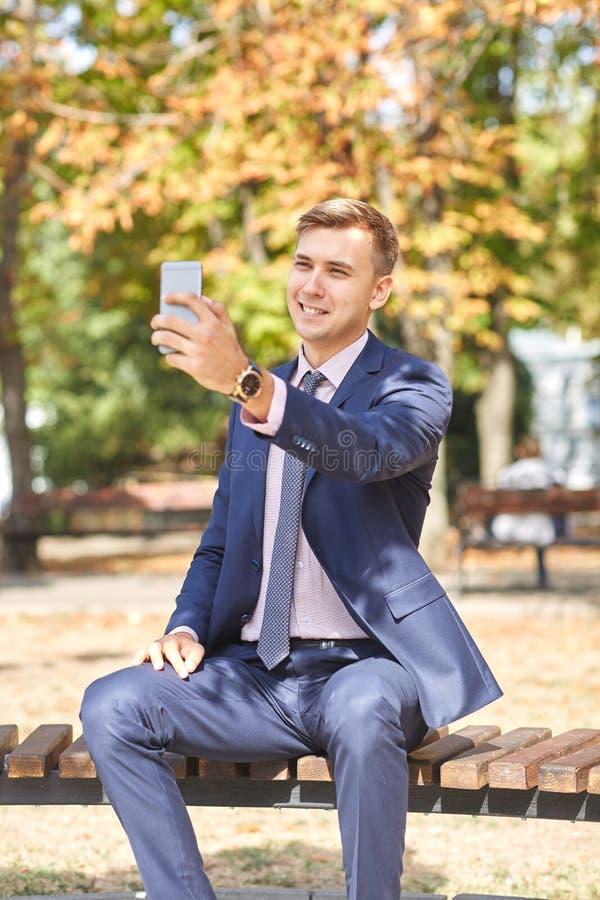 Ansenlig ung man som arbetar i parkera och poserar på kamera äganderätt för home tangent för affärsidé som guld- ner skyen till royaltyfria foton