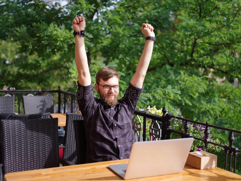 Ansenlig ung man som arbetar på bärbara datorn, medan sitta utomhus äganderätt för home tangent för affärsidé som guld- ner skyen royaltyfri bild