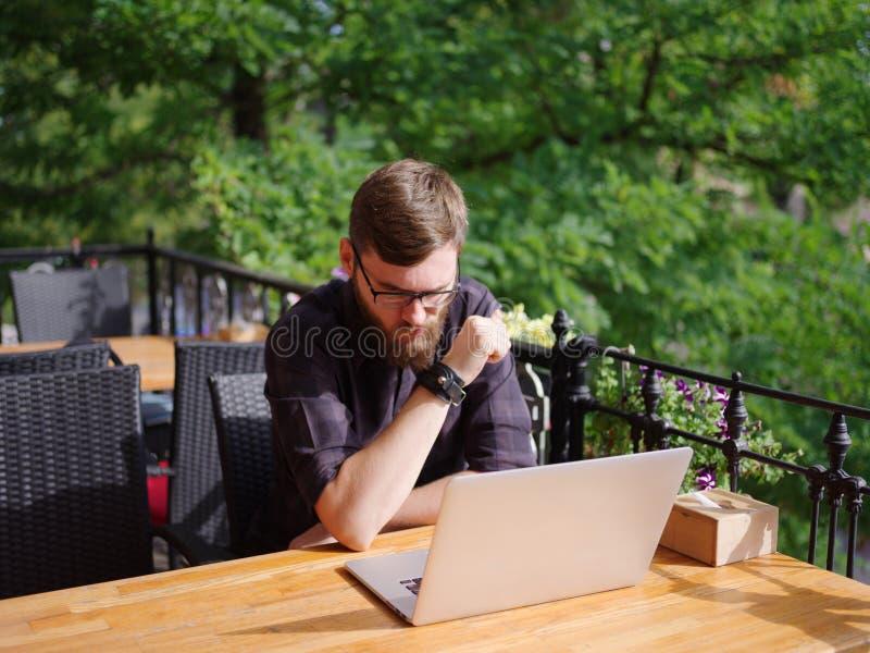 Ansenlig ung man som arbetar på bärbara datorn, medan sitta utomhus äganderätt för home tangent för affärsidé som guld- ner skyen arkivbild