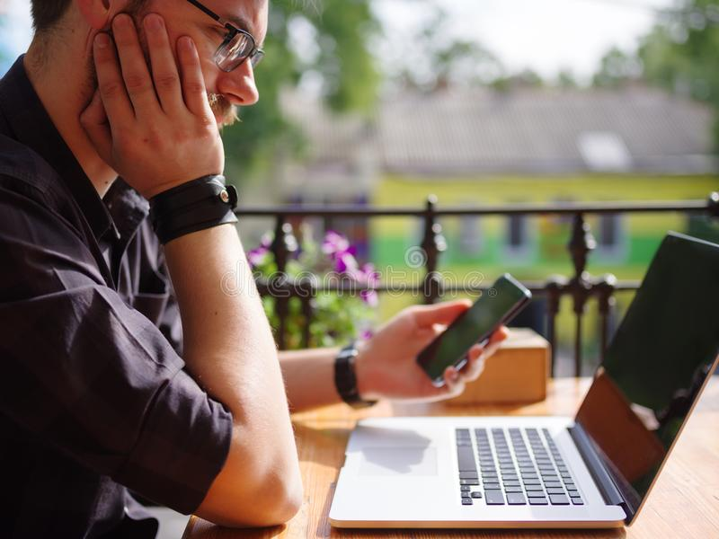 Ansenlig ung man som arbetar på bärbara datorn, medan sitta utomhus äganderätt för home tangent för affärsidé som guld- ner skyen royaltyfria foton