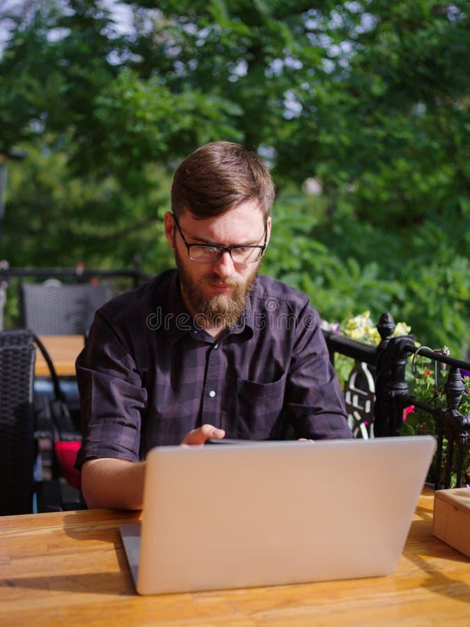 Ansenlig ung man som arbetar på bärbara datorn, medan sitta utomhus äganderätt för home tangent för affärsidé som guld- ner skyen royaltyfria bilder