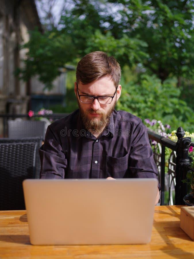Ansenlig ung man som arbetar på bärbara datorn, medan sitta utomhus äganderätt för home tangent för affärsidé som guld- ner skyen fotografering för bildbyråer