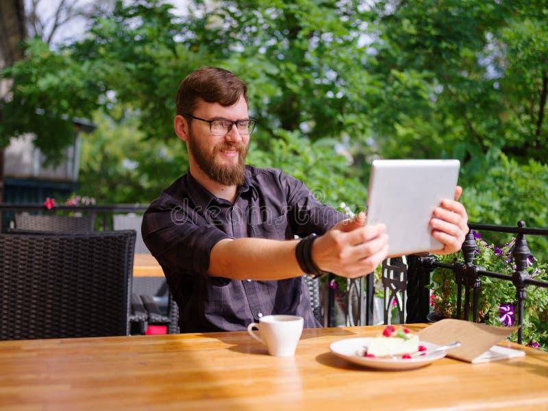Ansenlig ung man som arbetar på minnestavlan, medan sitta utomhus äganderätt för home tangent för affärsidé som guld- ner skyen t royaltyfri foto