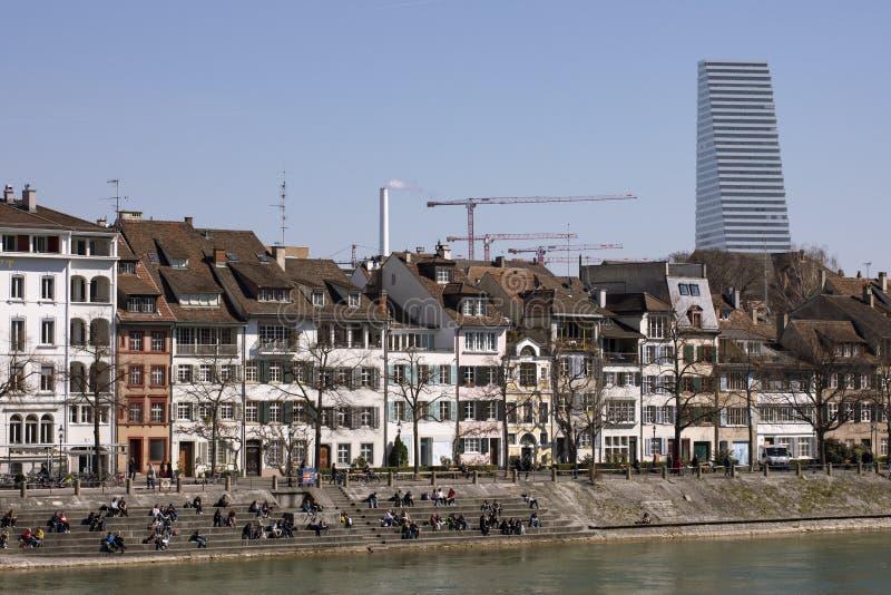 Ansicht über Basel-Stadtarchitektur Altbauten und moderner Wolkenkratzer Leute, die durch die Bank vom Rhein sitzen Blauer Himmel stockbild