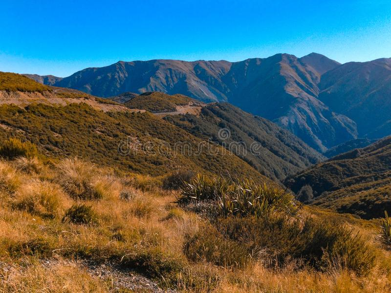 Ansicht über Berg-Hutt-Gebirgslandschaft an einem sonnigen Tag, nahe Methven, Südinsel, Neuseeland lizenzfreie stockfotografie