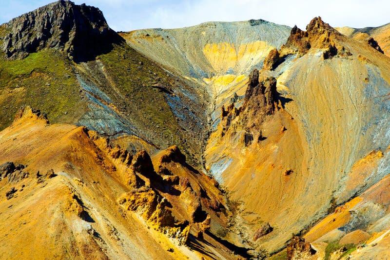 Ansicht über braune schroffe scharfe Bergspitzen des bunten gelben rötlichen Rosts stockbilder