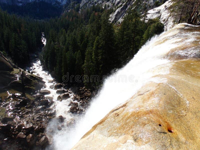 Ansicht über den Rand von frühlingshaften Fällen mit Regenbogen - Wasserfall in Yosemite Nationalpark, Sierra Nevada, Kalifornien stockbild