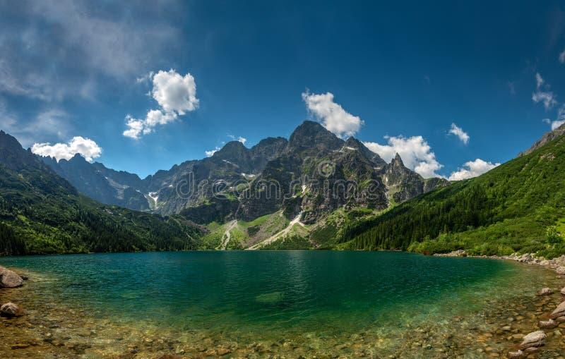 Ansicht über den Türkisfarbsee zwischen den hohen und felsigen Bergen stockbilder