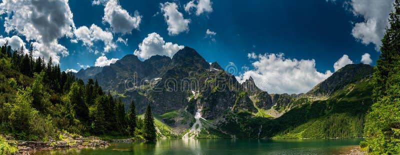 Ansicht über den Türkisfarbsee zwischen den hohen und felsigen Bergen stockfotografie